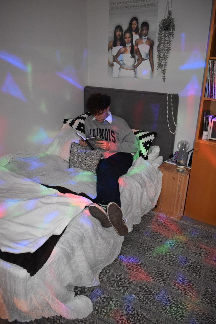 Student läser bok i sängen i internatrum